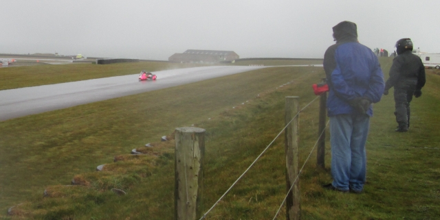a rain soaked track at anglesey circuit with a sidecar as wet people watch