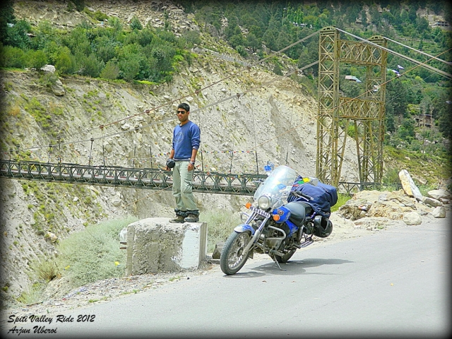 bridge amonst roacks and an indian rider with his bajaj avenger