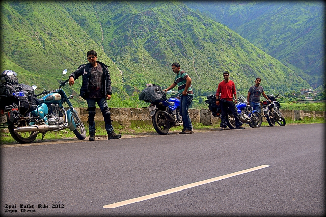 4 indian motorcyclists on tour in the spiti valley, stood by their motorcycles