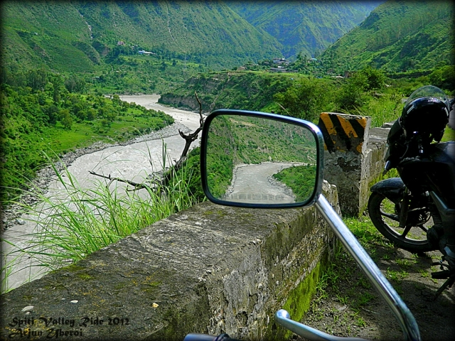 looking over a river flowing through a lush green valley, seen from a motorcycle
