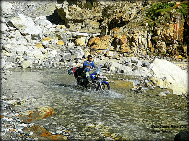 cossing a rocky river bed on a motorcycle in india