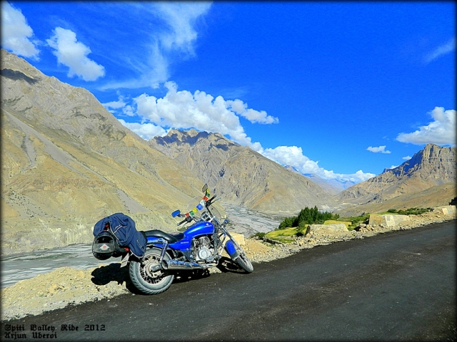 motorcycle set against massive hills and mountains in the spiti valley
