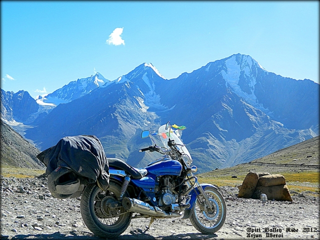 motorcycle in front of snow capped rocky peaks around the spiti valley india
