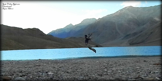 a man caught in mid air jumping next to a lake