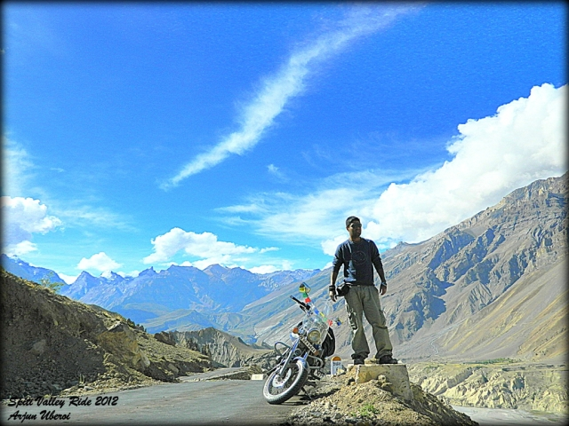 arjun posing next to his bike with massive mountains