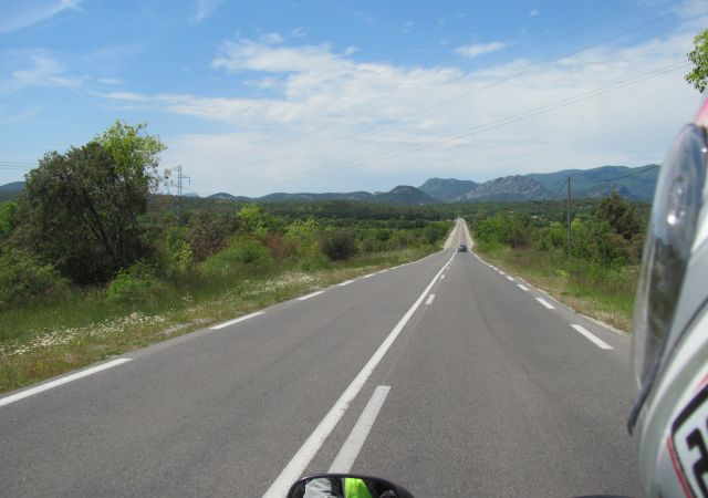a long straight empty road vanishes into the distance in southern france's sunshine