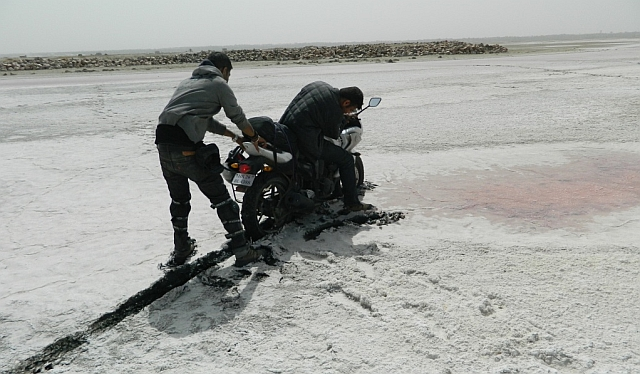 motorcycle stuck in the salt mud, being pulled out