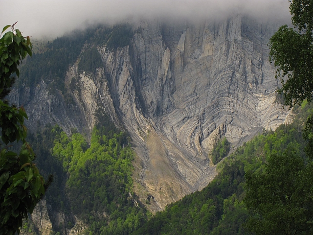 radical swirls and deformations in the rock strata and layers on a mountain side in the french alps
