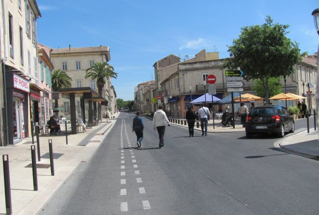 a busy broad french street with classic buildings either side in nimes