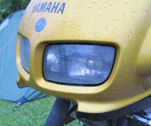 the headlamp reflector on a rain soaked bike with a wet tent behind in Auxonne france