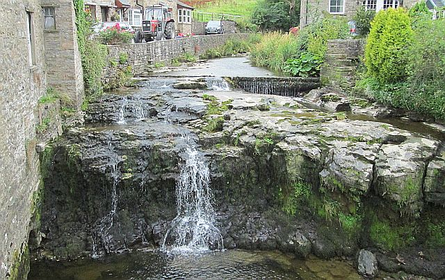 a small river cascading over rocks and a short waterfall in the centre of hawes in the dales