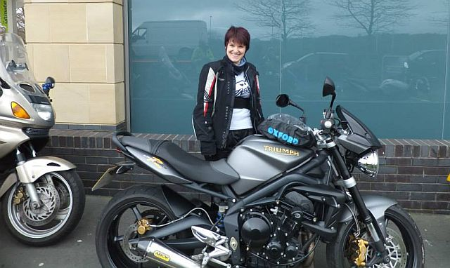 jr stands proudly behind her lowered street triple r