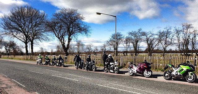 motorcycles in a line parked by the roadside