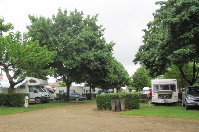 campervans line the gravel track through the rain soaked campsite