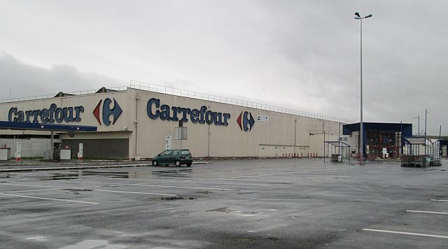 a dull off white slab of a building, carrefour supermarket in france