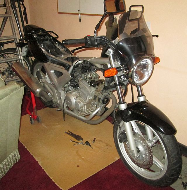 black cbf 250 with the rocker cover off in a living room