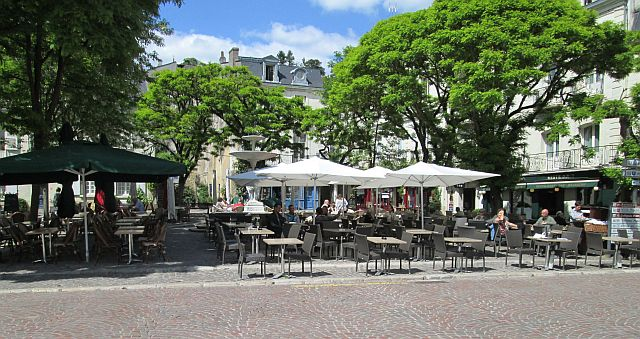 a broad town square filled with tables, chairs and canopies in chinon