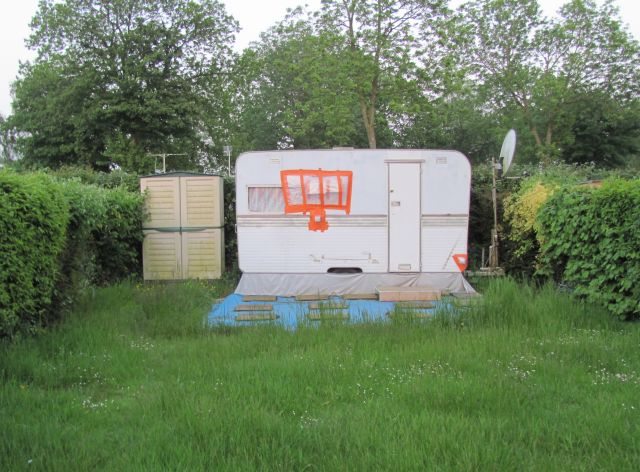 a small worn out caravan with patches in thick grass at the friaucourt camping municipal