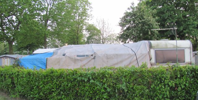 caravan and old tarpaulin making a scruffy ramshackle extension