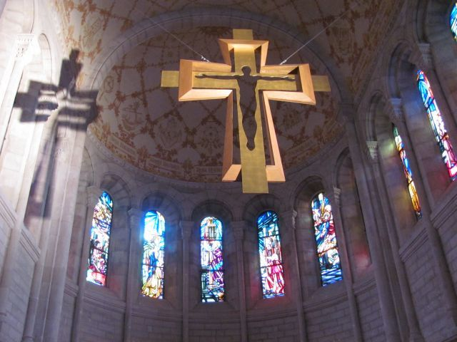 large gold coloured cross hanging from fine wires in the bastille, beautifully lit