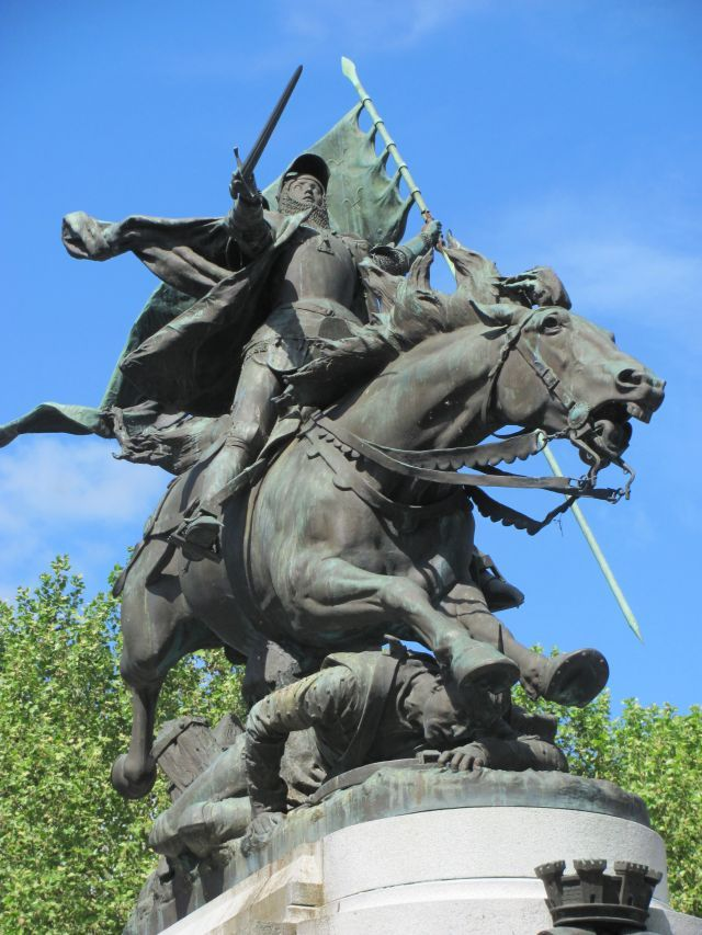 a massive bronze statue of joan of ark, on her horse mid battle