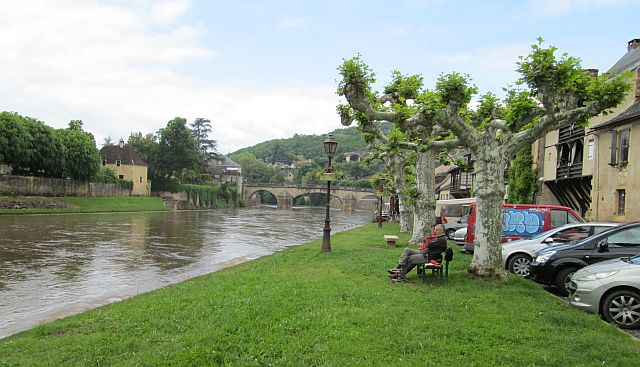 the swollen and mud red river flowing through pretty montignac
