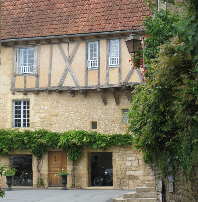 an ancient french house with a classic motorcycle in 2 windows ground floor