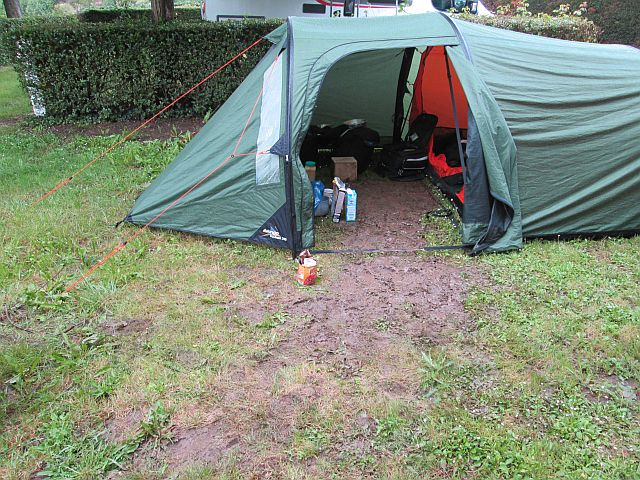 the tent and a muddy path from within the porch to the gravel track