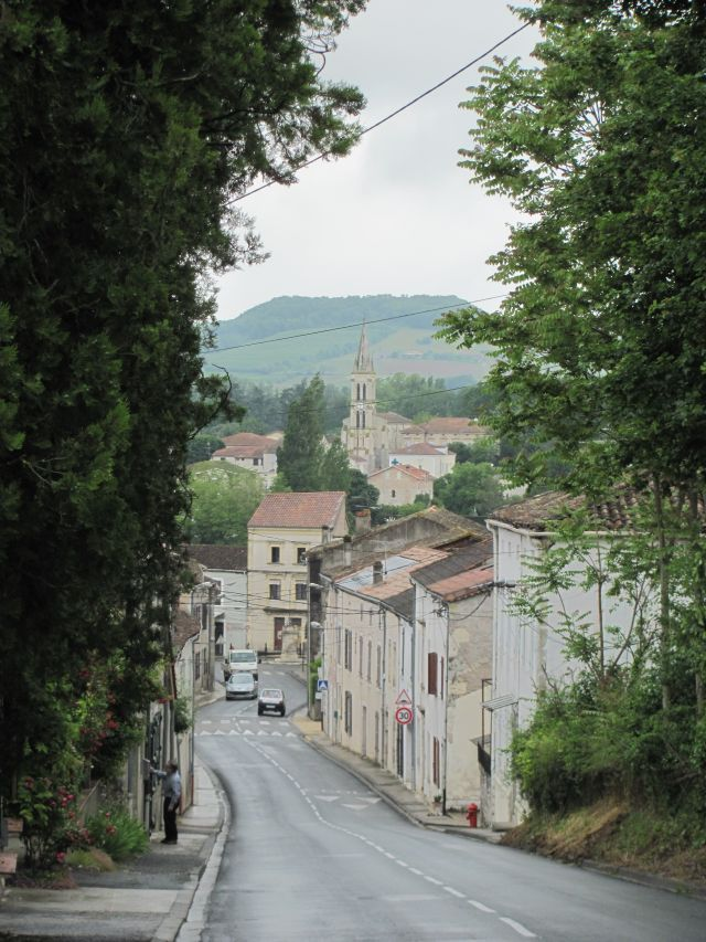a typical french street in penne d'agenais with houses and trees