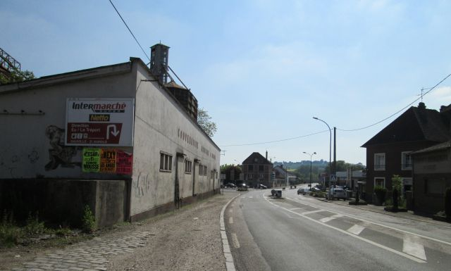 scruffy, plain, ordinary french street with dull buildings, telephone wires etc