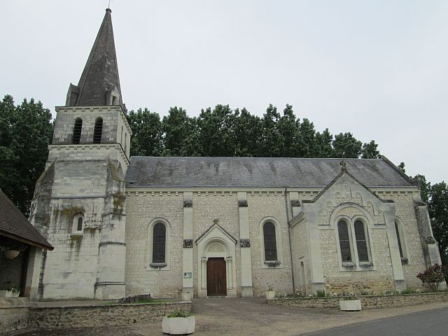 a french church with pointed spire and steep slate roof