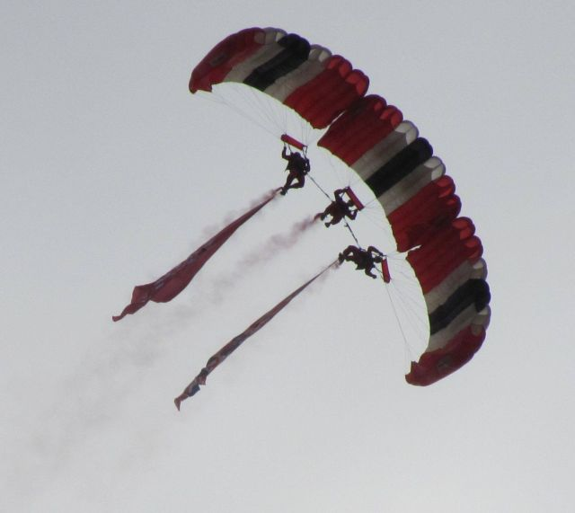 three red devils skydivers in tight formation