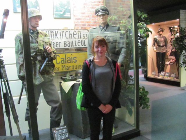 sharon stands in front of a glass cabinet filed with world war 2 uniforms on display
