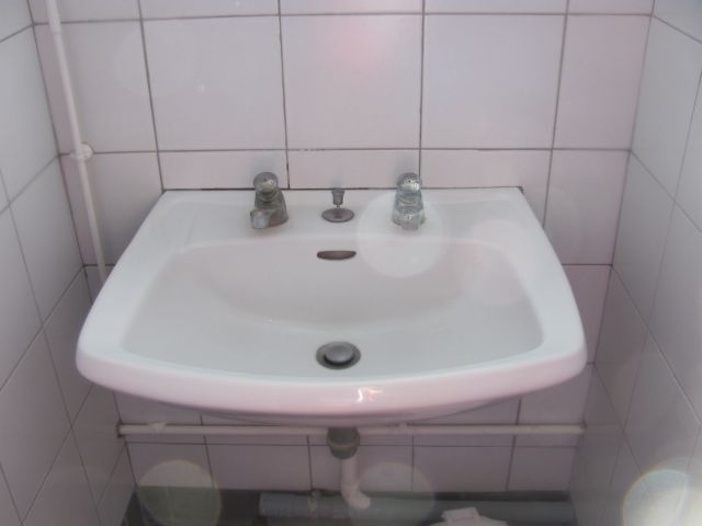 a single sink in a small white tiled cubicle