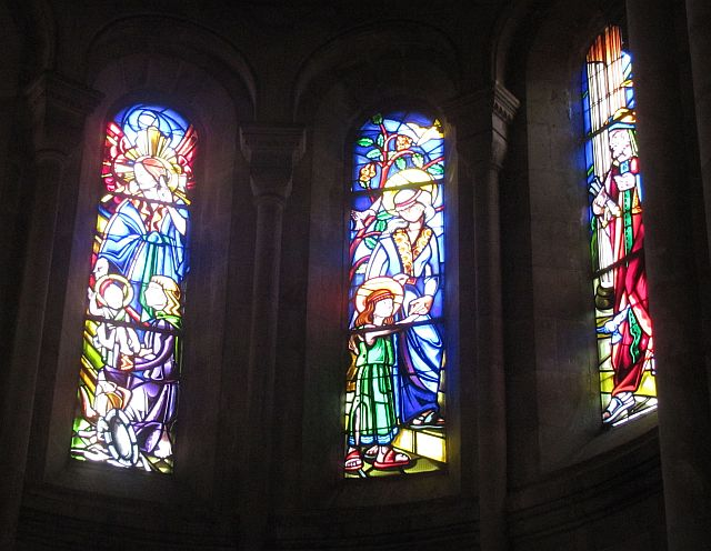 3 tall arched stained glass windows with the light shining through