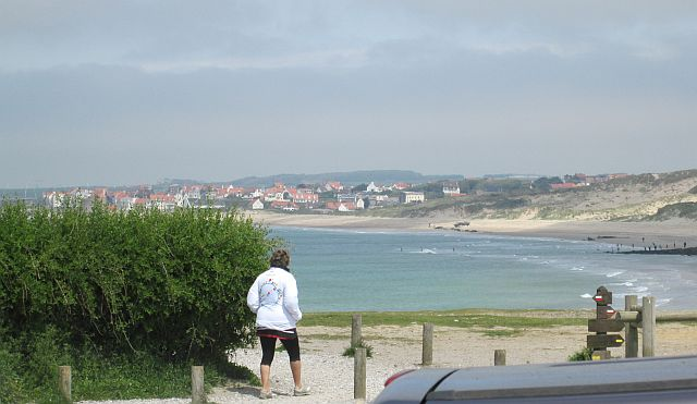 a broad sandy bay with the town of wimeraux in the background