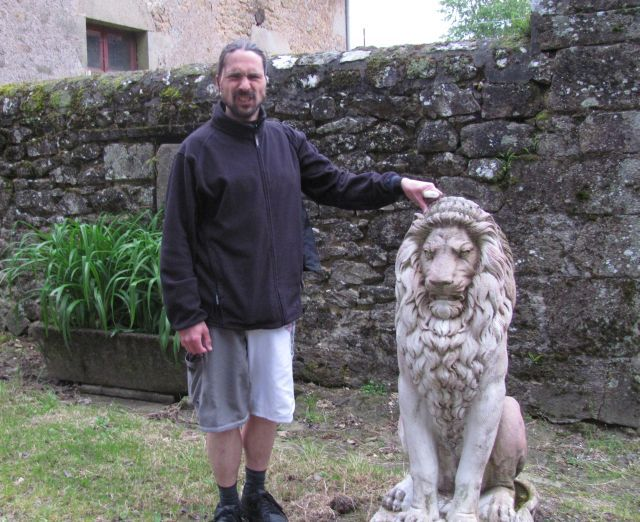 the bf stood next to a stone rampant lion pulling a growling face