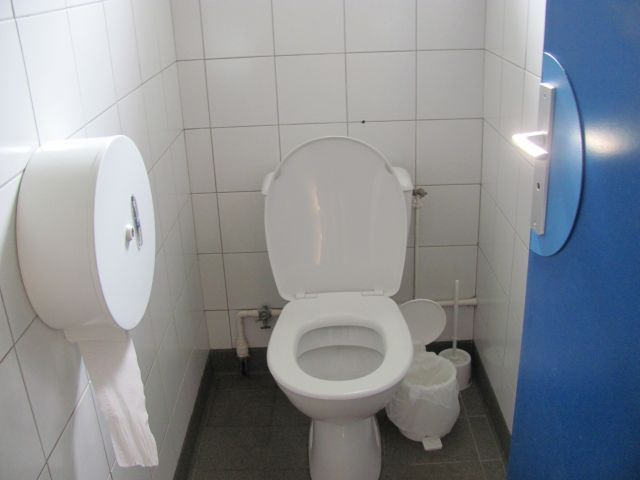 toilet in a small white tiled cubicle