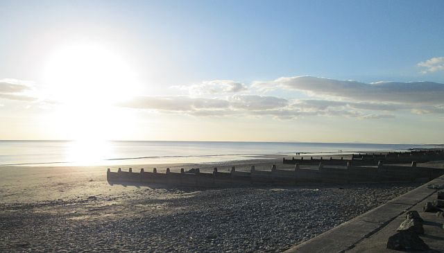 a bright sunset over a shadowy beach at tywyn mid wales
