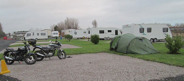 the 125 parked on gravel by the tent at the campsite near blackpool
