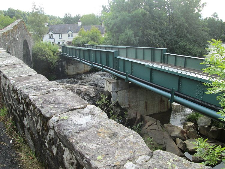the old stone bride and the new steel bridge in green at tummel bridge