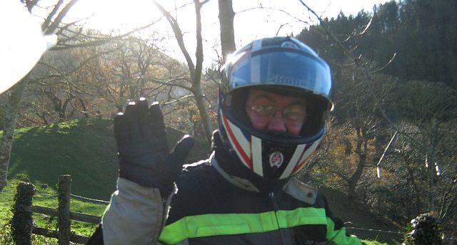 a biker waving to the camera quite close up