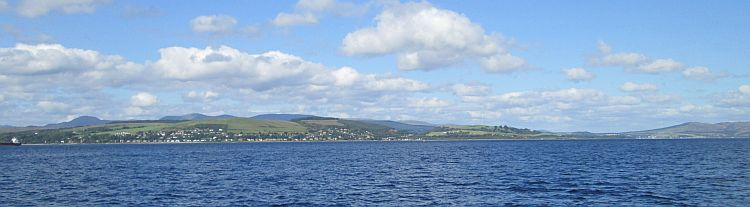 a wide view of the firth of clyde. blue waters with hills and mountains in the distance