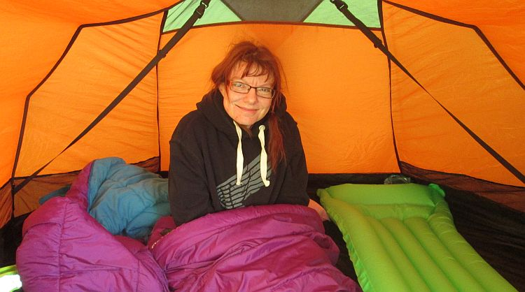 the gf smiles from her sleeping bag in the tent at the campsite