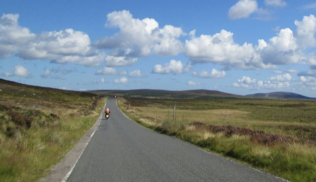 the gf rides way up ahead on a vast wide open moorland and blue skies