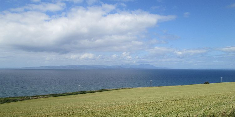 a crop filled field, then the sea and the isle of arran in the distance