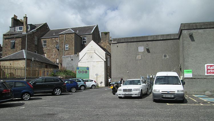 an ordinary car park behind some ordinary buildings at maybole co-op