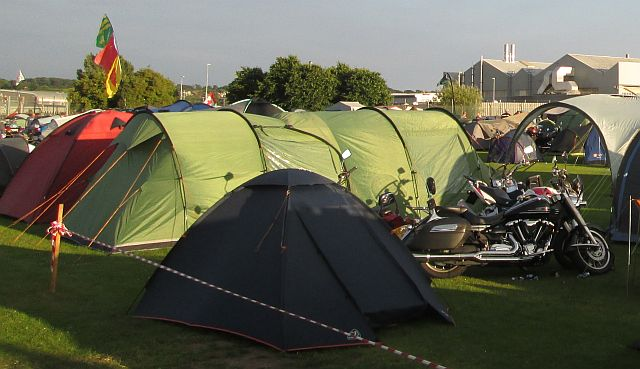 several tents of various sizes and style in the rally field