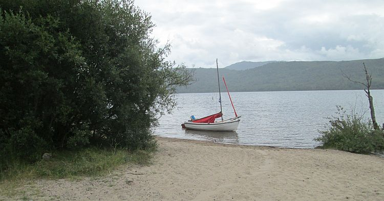 a small sandy beach runs into loch rannoch complete with tiny sailing dinghy