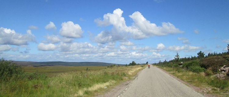 Sharon in the distance riding across a long vast open moor in the sun
